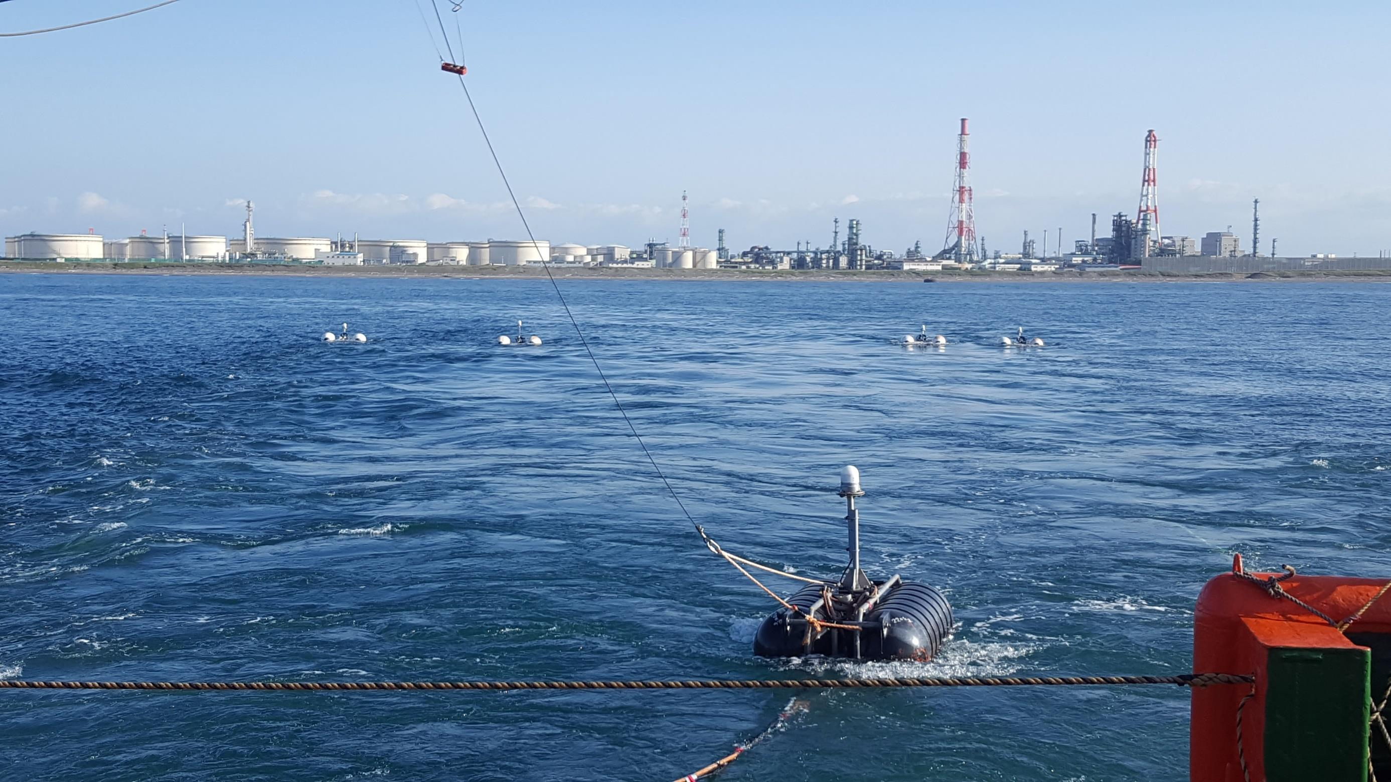 IMAGE OF SEISMIC SOURCE FLOATING ON THE WATER WITH THE TOMAKOMAI PORT IN THE DISTANCE
