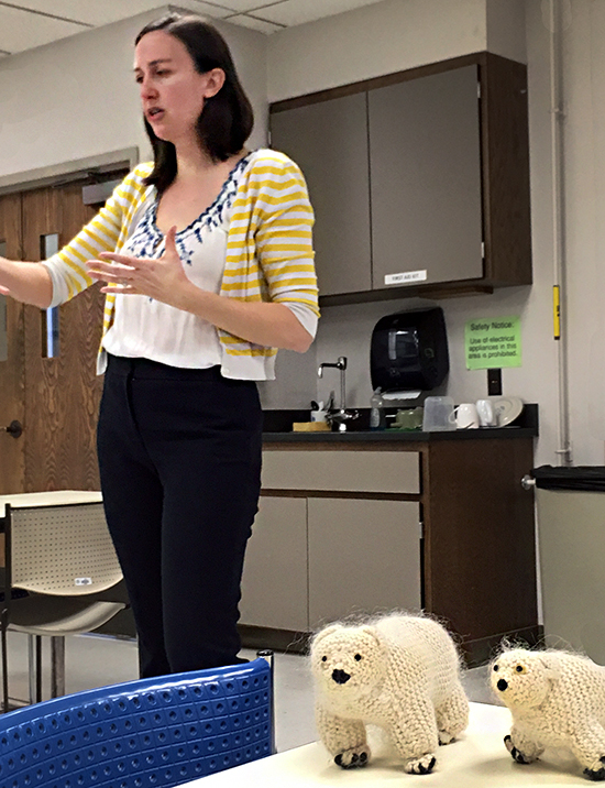 Caroline Reck talks with polar bear puppets in front of her.