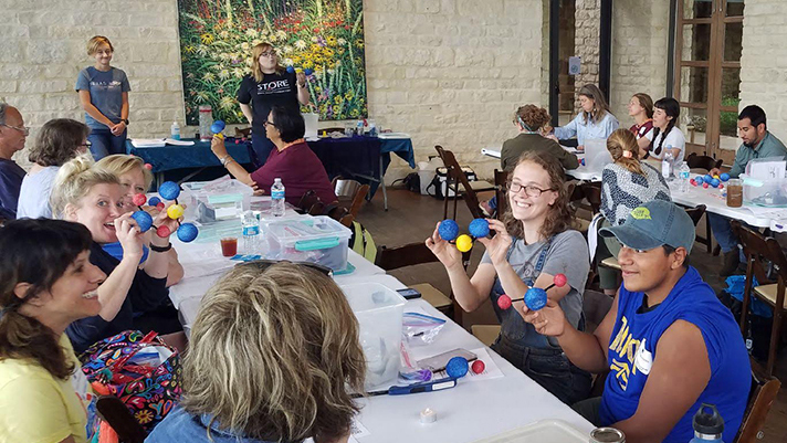 Photo of a group of about 25 teachers around a U shaped group of tables holding CO2 molecules made from pipe cleaners and styrofoam balls