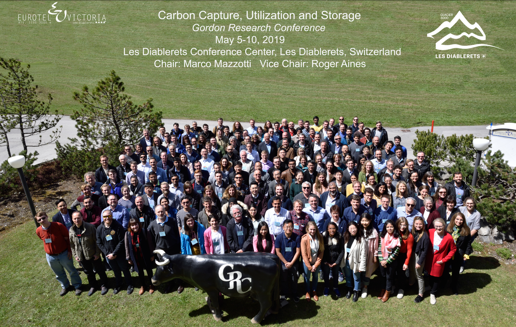 Approximately 200 of the conference attendees stand in a grassy field in Switzerland