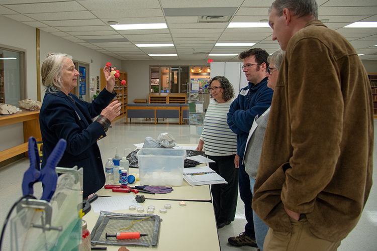 Susan Hovorka shows participants around a table of demonstrations, the molecular structure of CO2