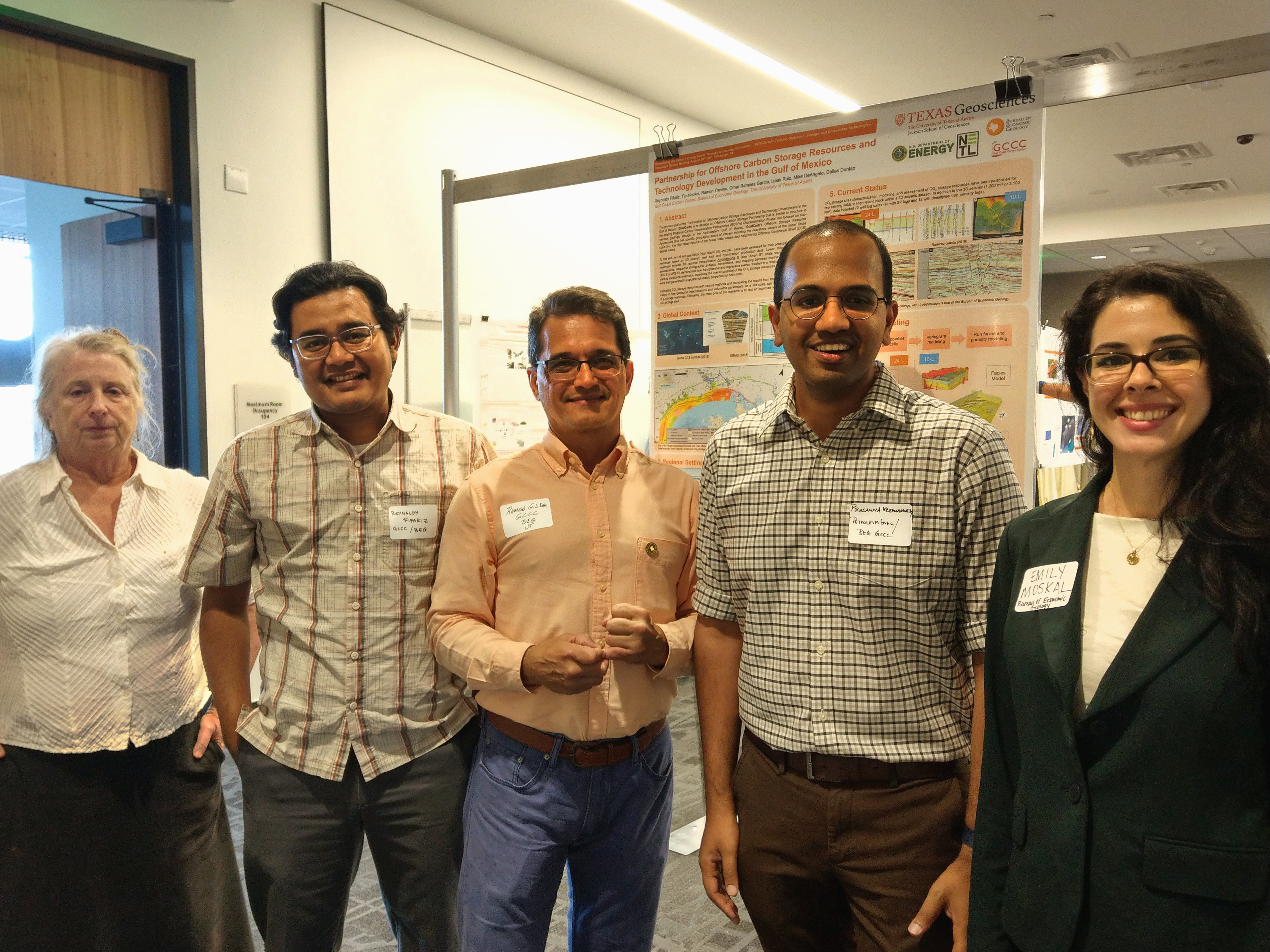 Five GCCC researchers stand in front of one of the posters presented at the expo