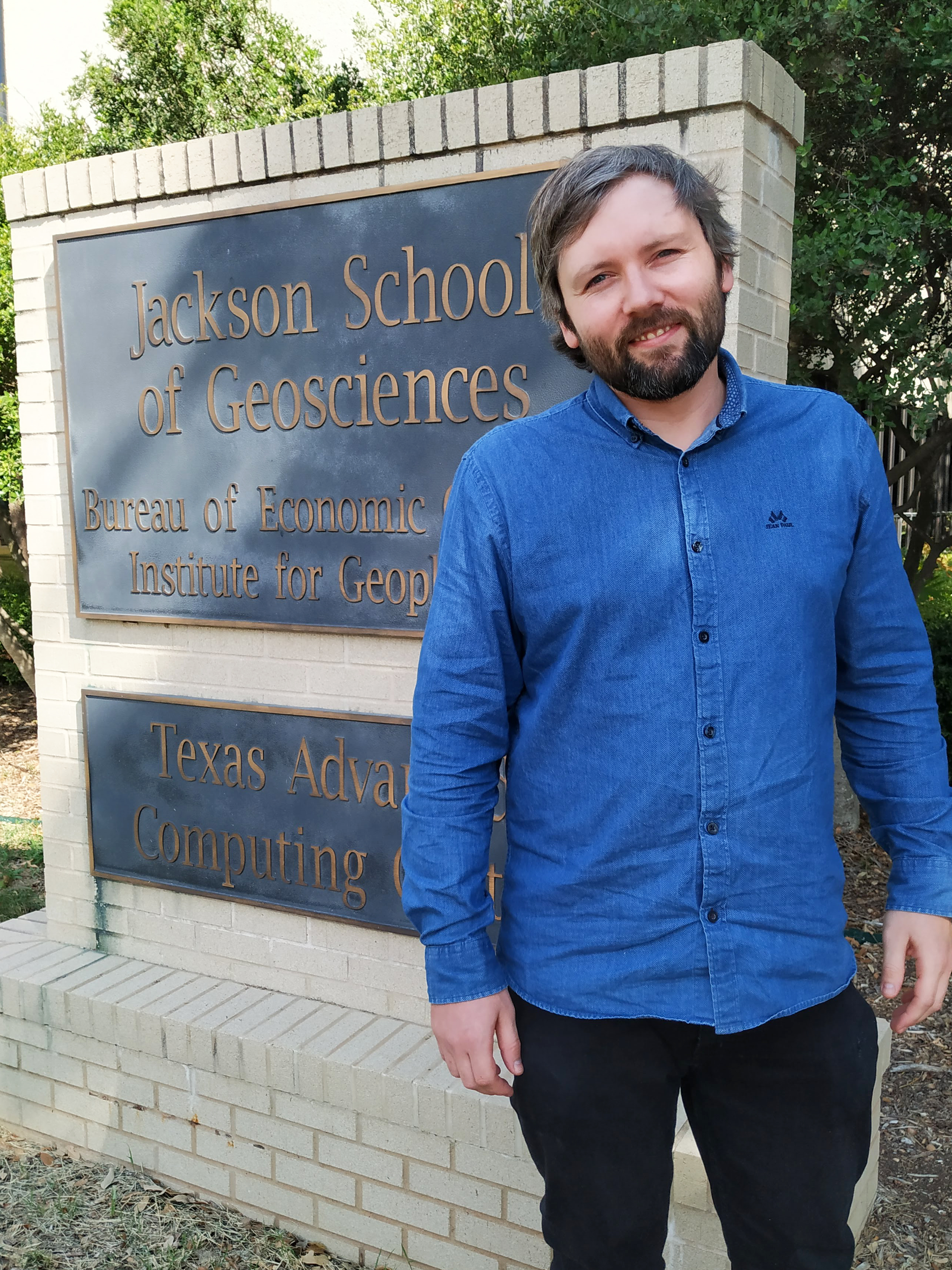 Kristian stands in front of the Jackson School of Geosciences/Bureau of Economic Geology sign in front of the building