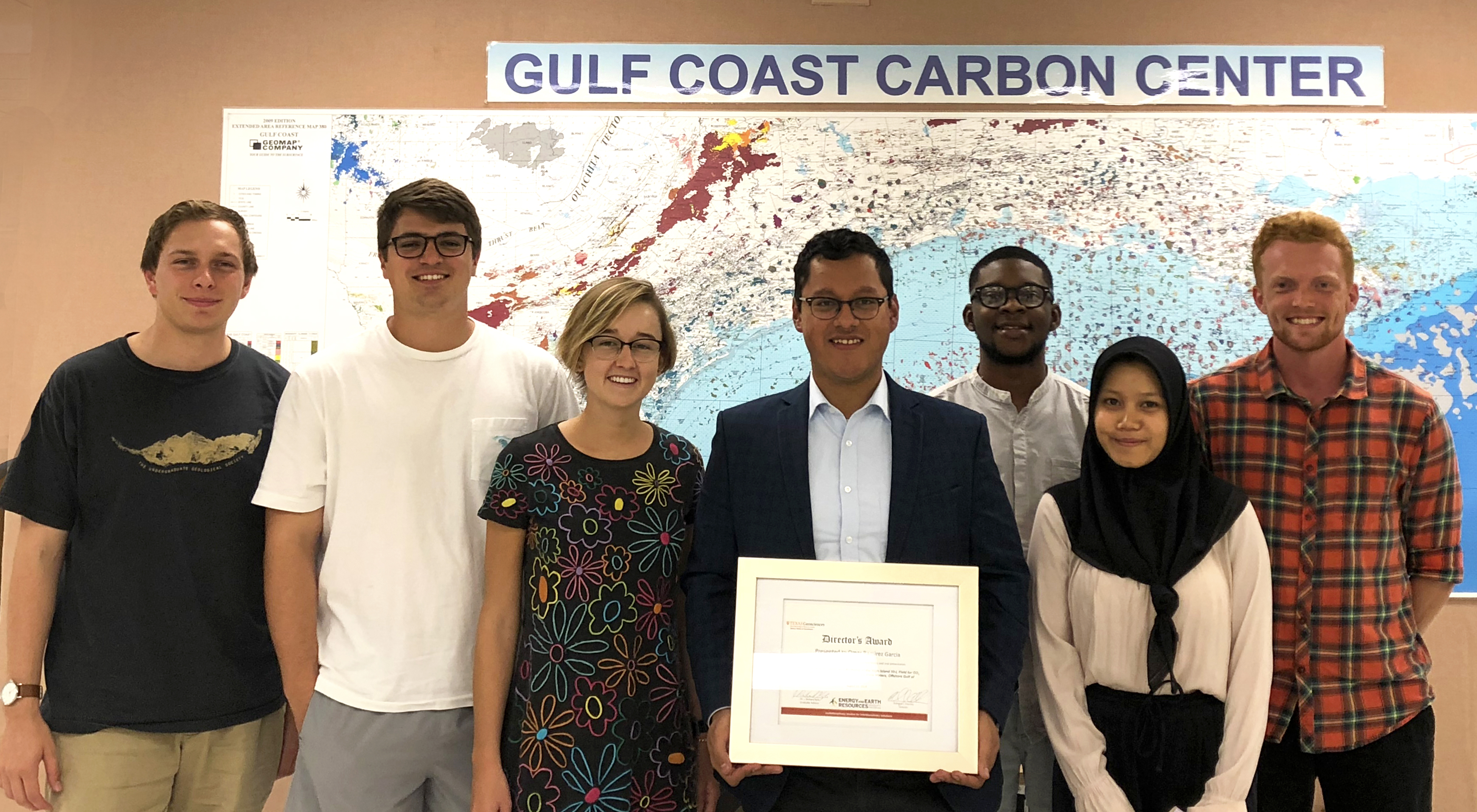 Omar stands in the middle of the incoming master's graduate students with his director's award for excellent thesis and Margaret, an undergraduate researcher
