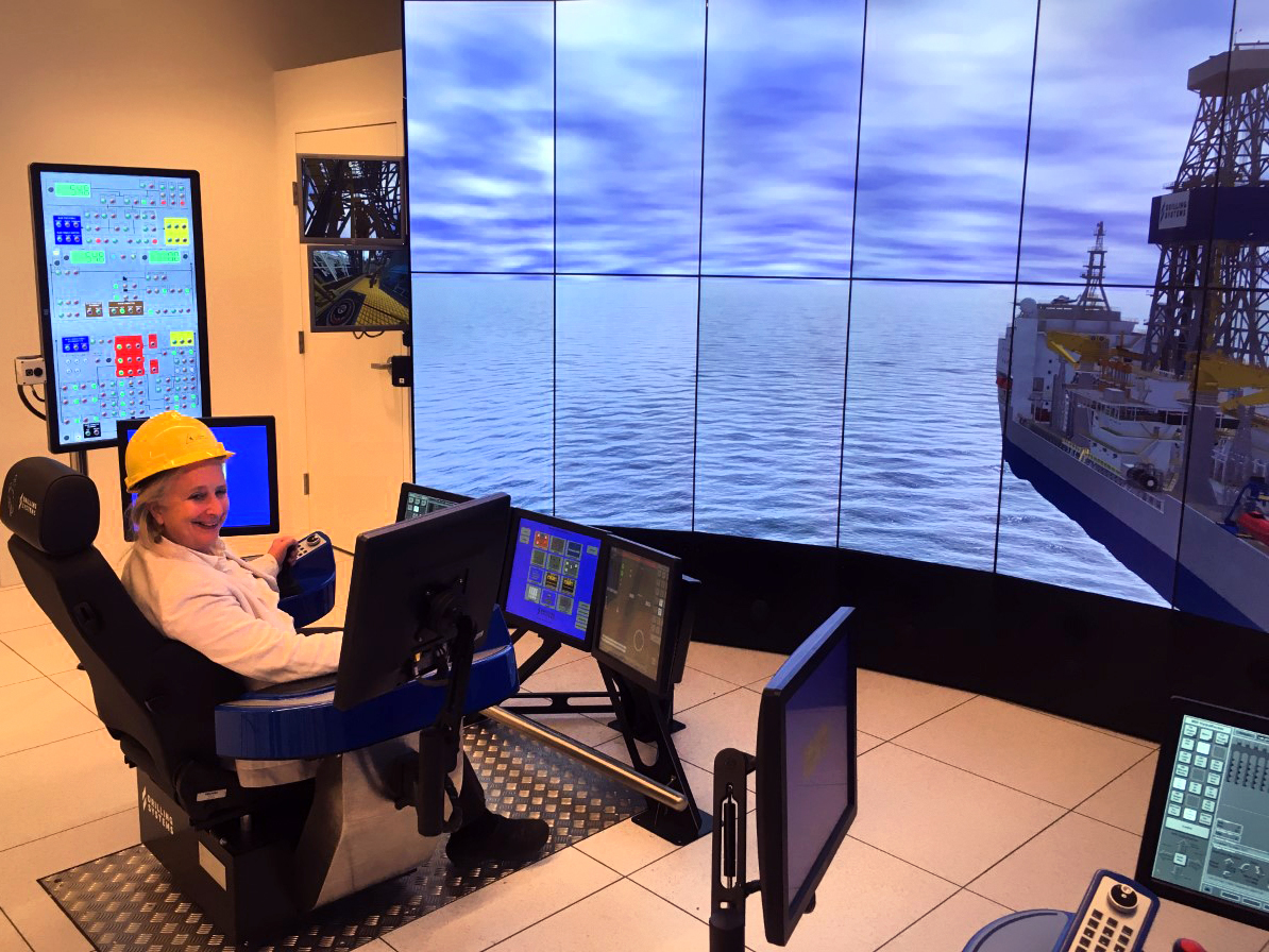 Sue sits in front of monitors and a large screen (simulator) that shows a drilling rig out on sea