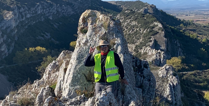 Photo of Izaak in field gear including a reflective vest and hard hat at the top of a mountain ridge in Spain
