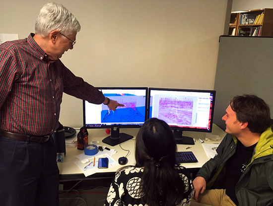 photo of rob finley pointing to the computer monitor of seismic data and subsurface models